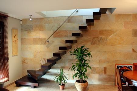 detalle muy decorativo de escalera volada en madera de wengu visualmente ocupa poco espacio en la estancia al ser recta y sin pasamanos en la parte